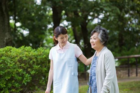 シニア女性の歩行を介助する介護福祉士の写真素材 [FYI01857063]
