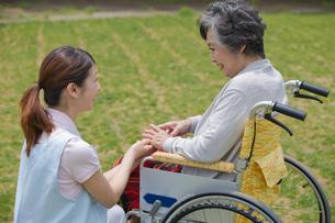 車いすに乗るシニアの手に触れる介護福祉士の写真素材 [FYI01857074]