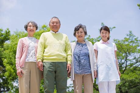 並んで立つシニアの男女と介護福祉士の写真素材 [FYI01857125]
