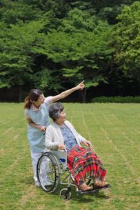 シニア女性の車いすを押す介護福祉士の写真素材 [FYI01857195]