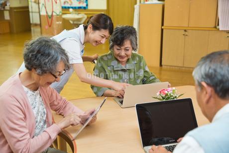 パソコンを使うシニアと教える介護福祉士の写真素材 [FYI01857251]