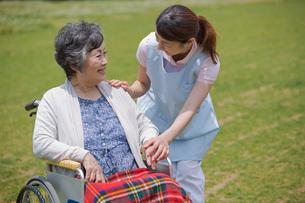 車いすに乗るシニアの手を握る介護福祉士の写真素材 [FYI01857286]