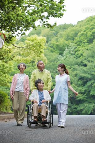 公園を散歩するシニアの男女と介護福祉士の写真素材 [FYI01857301]