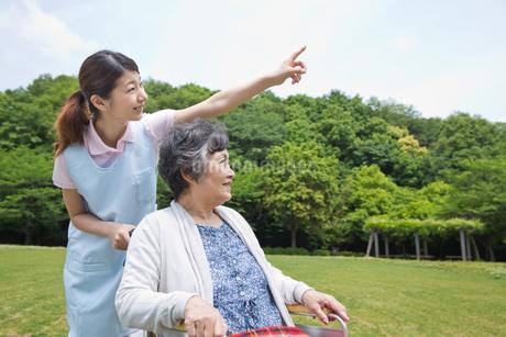 シニア女性の車いすを押す介護福祉士の写真素材 [FYI01857350]