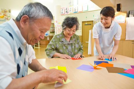 折り紙を折るシニアと介護福祉士の写真素材 [FYI01857386]