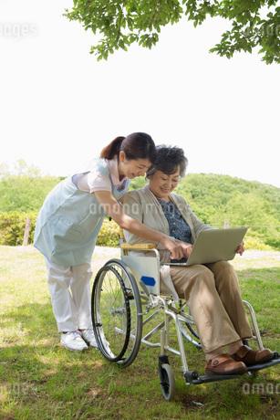 公園でパソコンを見るシニアと介護福祉士の写真素材 [FYI01857402]