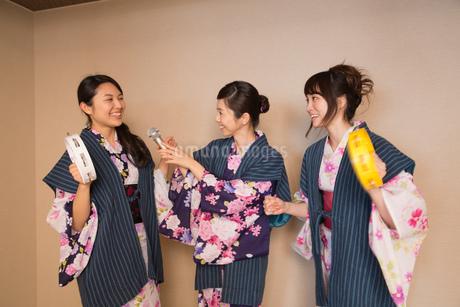 浴衣姿でカラオケを楽しむ若い女性3人の写真素材 [FYI01857470]