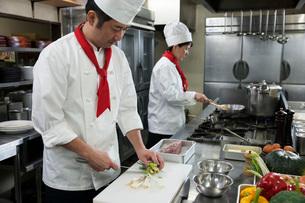厨房で働く二人の調理師の写真素材 [FYI01857503]