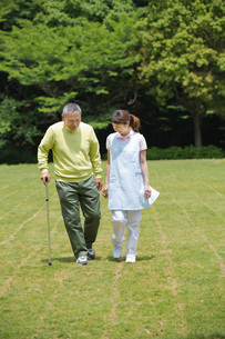 シニア男性の歩行を介助する介護福祉士の写真素材 [FYI01857565]