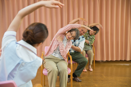 体操をするシニアと介護福祉士の写真素材 [FYI01857591]