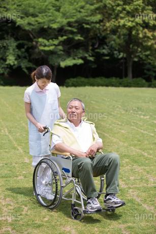 シニア男性の車いすを押す介護福祉士の写真素材 [FYI01857593]