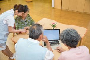 パソコンを使うシニアと教える介護福祉士の写真素材 [FYI01857635]
