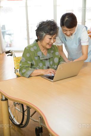 パソコンを使うシニアと教える介護福祉士の写真素材 [FYI01857735]