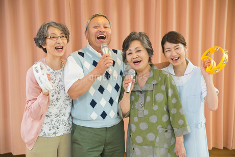 カラオケを楽しむシニアと介護福祉士の写真素材 [FYI01857736]