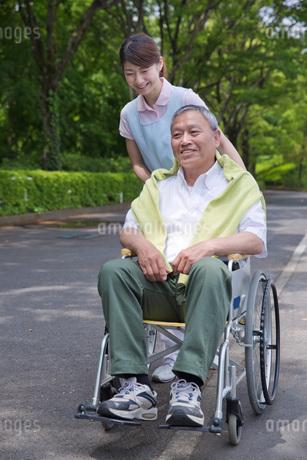 シニア男性の車いすを押す介護福祉士の写真素材 [FYI01857738]