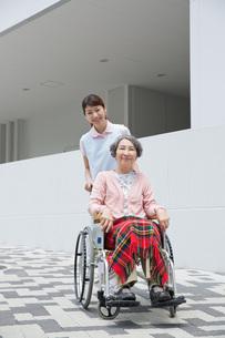 シニア女性の車いすを押す介護福祉士の写真素材 [FYI01857853]