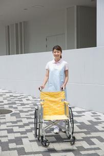 車いすを押す介護福祉士の写真素材 [FYI01857870]