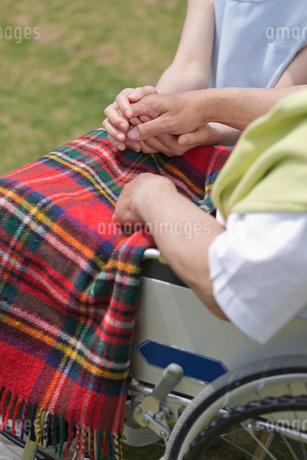 車いすに乗るシニアの手を握る介護福祉士の写真素材 [FYI01857888]