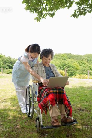 公園でパソコンを見るシニアと介護福祉士の写真素材 [FYI01857933]