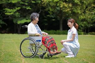 公園で休む車いすのシニア女性と介護福祉士の写真素材 [FYI01858025]
