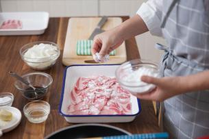 豚薄切り肉に小麦粉をまぶす女性の写真素材 [FYI01858165]