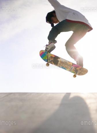 スケートボードでジャンプする日本人男性の写真素材 [FYI01860701]