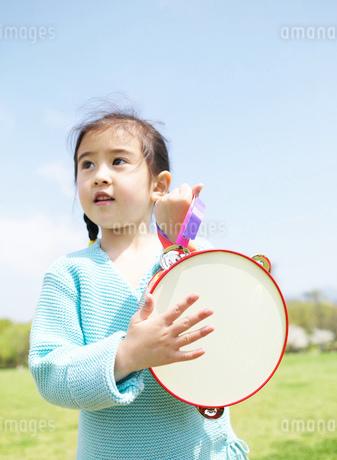 タンバリンを演奏する日本人の女の子の写真素材 [FYI01861031]