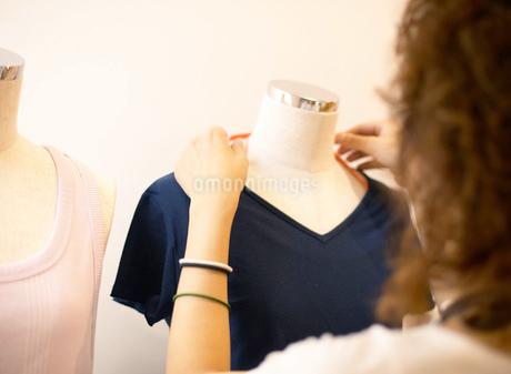 マネキンの洋服に触れる女性の写真素材 [FYI01863731]