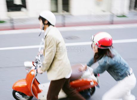 バイクを押すカップルの写真素材 [FYI01864580]