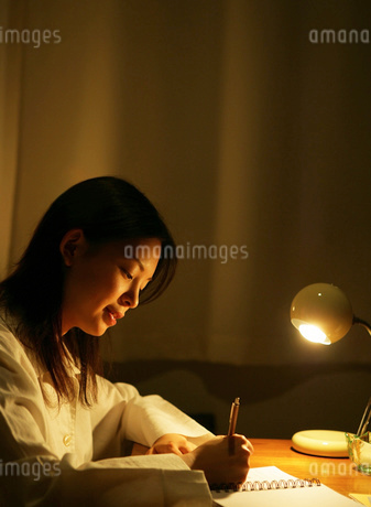 暗い部屋で文字を書いている日本人女性の写真素材 [FYI01865247]