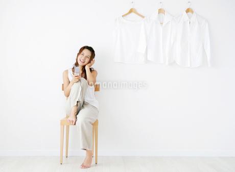 音楽を聴きながら携帯電話を持つ日本人女性の写真素材 [FYI01865346]