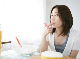 ケーキを作りながら味見をする日本人女性の写真素材 [FYI01865503]