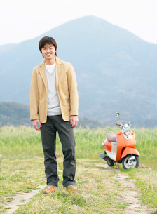 山道に立つ男性とバイクの写真素材 [FYI01865784]