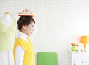 本を頭に乗せる女性の写真素材 [FYI01865815]