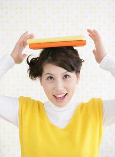 本を頭に乗せる笑顔の女性の写真素材 [FYI01865820]