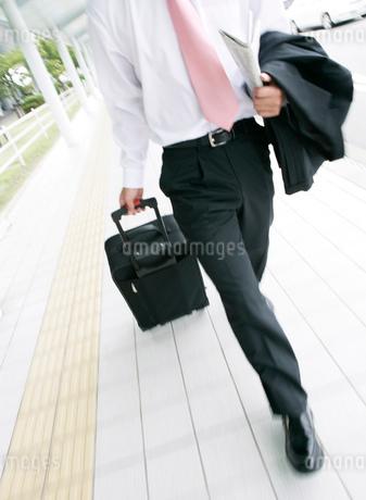 キャリーバッグを持ちながら歩くビジネスマンの写真素材 [FYI01865859]