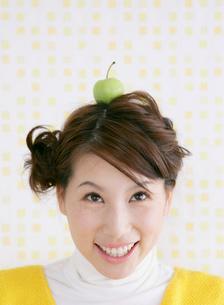 果物を頭に乗せる女性の写真素材 [FYI01866073]
