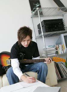 ギターを持ち楽譜を書く日本人男性の写真素材 [FYI01866339]