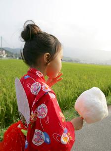綿菓子を手に持つ浴衣姿の女の子の写真素材 [FYI01866576]