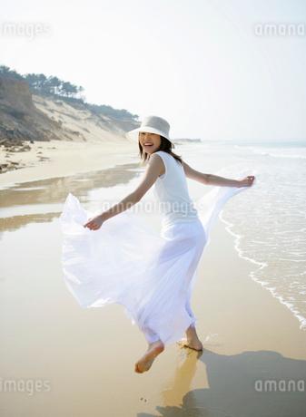 海辺を走るワンピースの女性の写真素材 [FYI01867062]