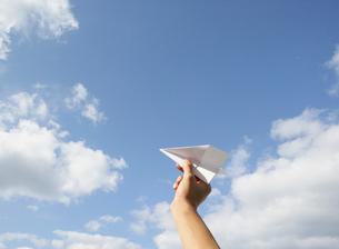 紙飛行機を持つ手と青空の写真素材 [FYI01867336]