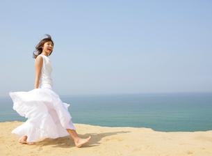 砂浜を歩く女性の写真素材 [FYI01867342]
