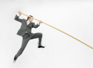 走り高跳びをするビジネスマンの写真素材 [FYI01867386]
