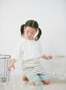 ゴミ箱にビンを入れる女の子の写真素材 [FYI01867720]