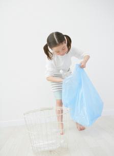 ゴミ箱にビンを入れる女の子の写真素材 [FYI01867731]