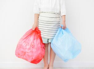 2つのゴミ袋を持つ女の子の写真素材 [FYI01867979]