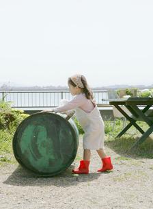ドラム缶を押す女の子の写真素材 [FYI01868283]