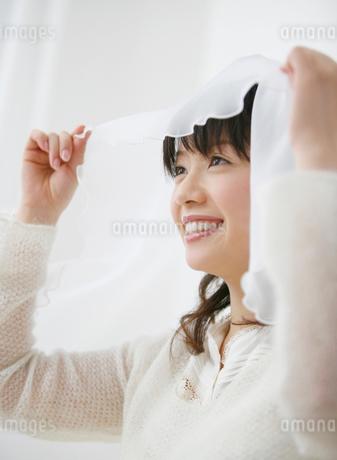 ベールを持って微笑む女性の写真素材 [FYI01868393]