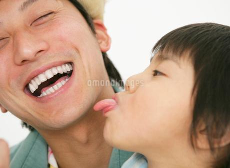 娘に舌であごを舐められている父親の写真素材 [FYI01868630]