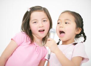 マイクを持って歌う二人の女の子の写真素材 [FYI01868745]